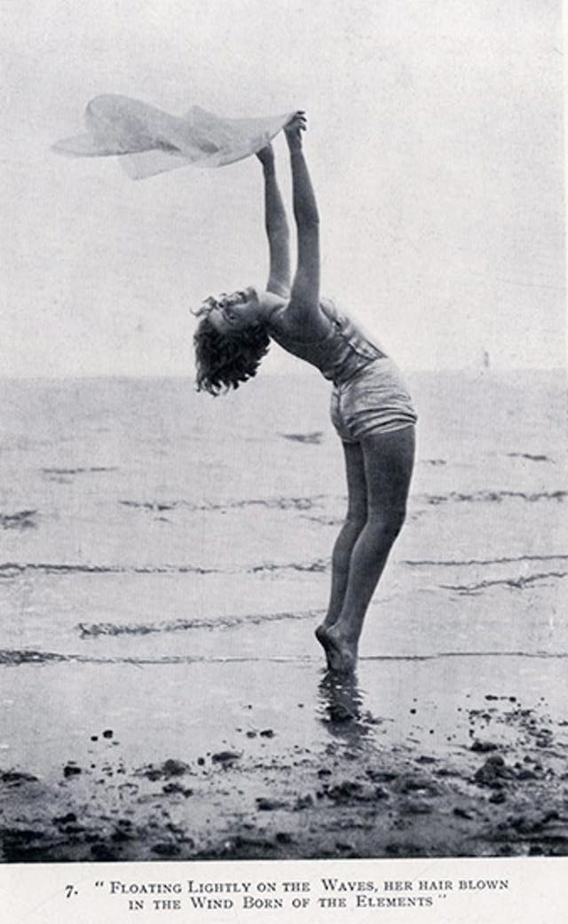 Woman exercising on a beach with a scarf in her raised arms