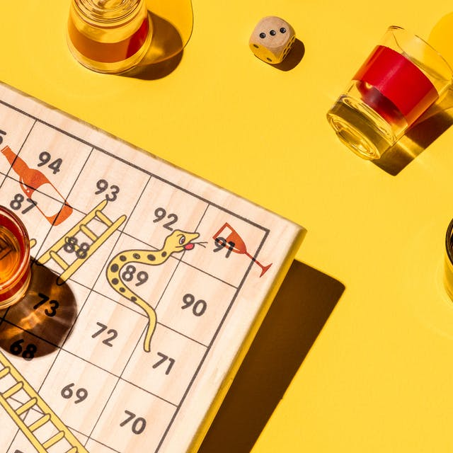 Photograph of a board game of snakes and ladders made of wood, sitting on a yellow background. The snakes on the board game are drinking alcohol.  Surrounding the board are five shot glasses, three of which are brimming with alcohol, and two which have been spilled.  In the  centre right of the frame there are two dice reading the numbers five and three.