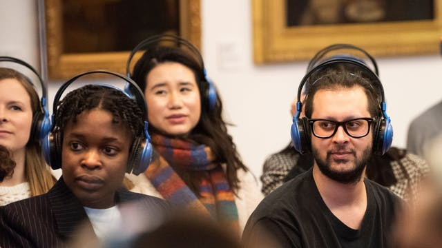 A photograph of a group of people at an event in the Reading Room in Wellcome Collection. They are all wearing headphones. Behind them are paintings on the wall.