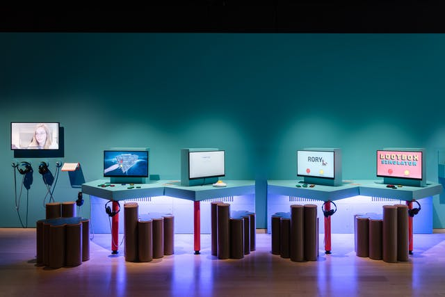 Photograph of an exhibition space showing 4 display screens mounted on tabletops with 5 chairs made out of brown cylinders. Hanging from the tables are sets of headphones. On one screen is the word, Rory, on another are the words, Lootbox simulator.