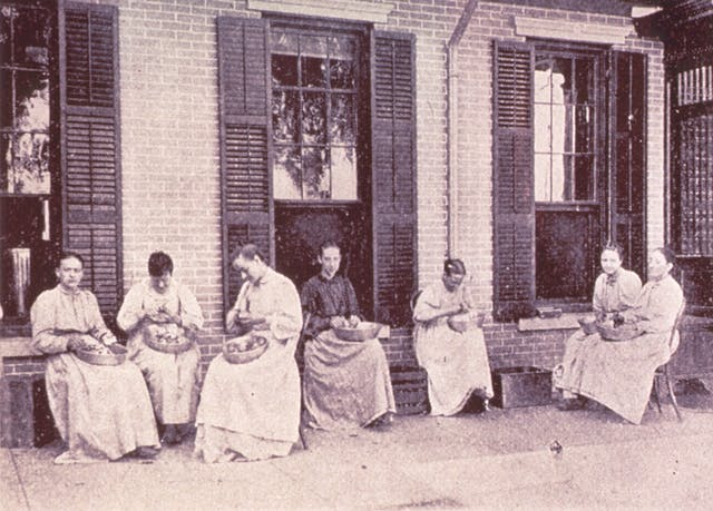 A group of women seated outside a large building, peeling vegetables into bowls on their laps