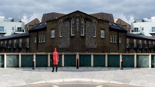 Photographic panorama showing a street scene with part of a road, a pavement, the handrail of a bridge and in the distance industrial brick buildings. The panorama is mirrored down its vertical centre line except that a small human figure in a red coat standing on the pavement looking away from the camera appears in the left half, but not in the right half.