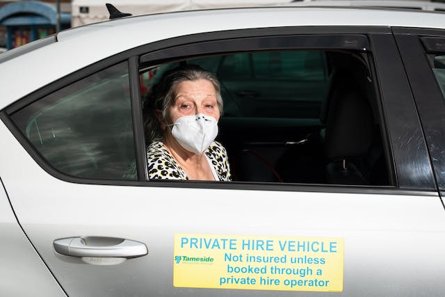 Photographic flash lit portrait through the open side window of a stationary car. The car is silver and the front of the car is facing to the right. On the door is a large sign with the words,