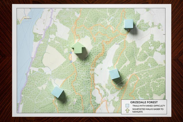 Photograph of a warm wood grained, polished tabletop from above. Resting on the table is a rectangular map showing roads, lakes, and the contours of hills. Resting on the map at strategic locations are four three dimensional shapes, a light green arrow and three light blue cubes. To the bottom right of the map is a legend titled,