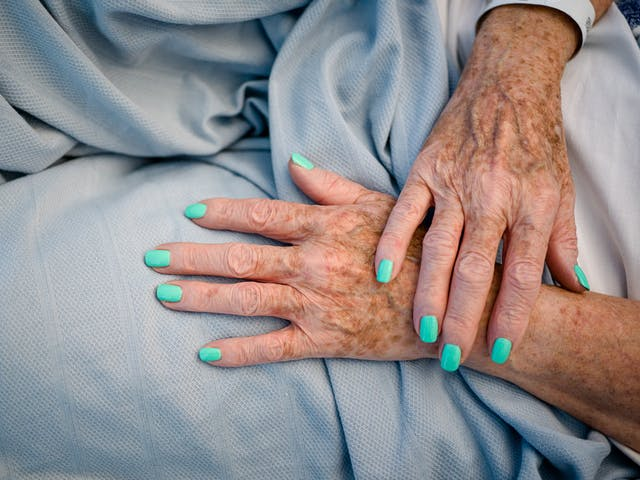 Photograph of the hands of a patient with bright turquoise painted fingernails, resting on a light blue hospital bedsheet.