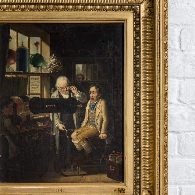 Photograph of a painting in a gilt frame depicting a white-haired man wearing glasses tapping the knee of a seated man with a pronged metal rod. The seated man has a shocked expression. Behind the framed painting are the bricks of a whitewashed wall.
