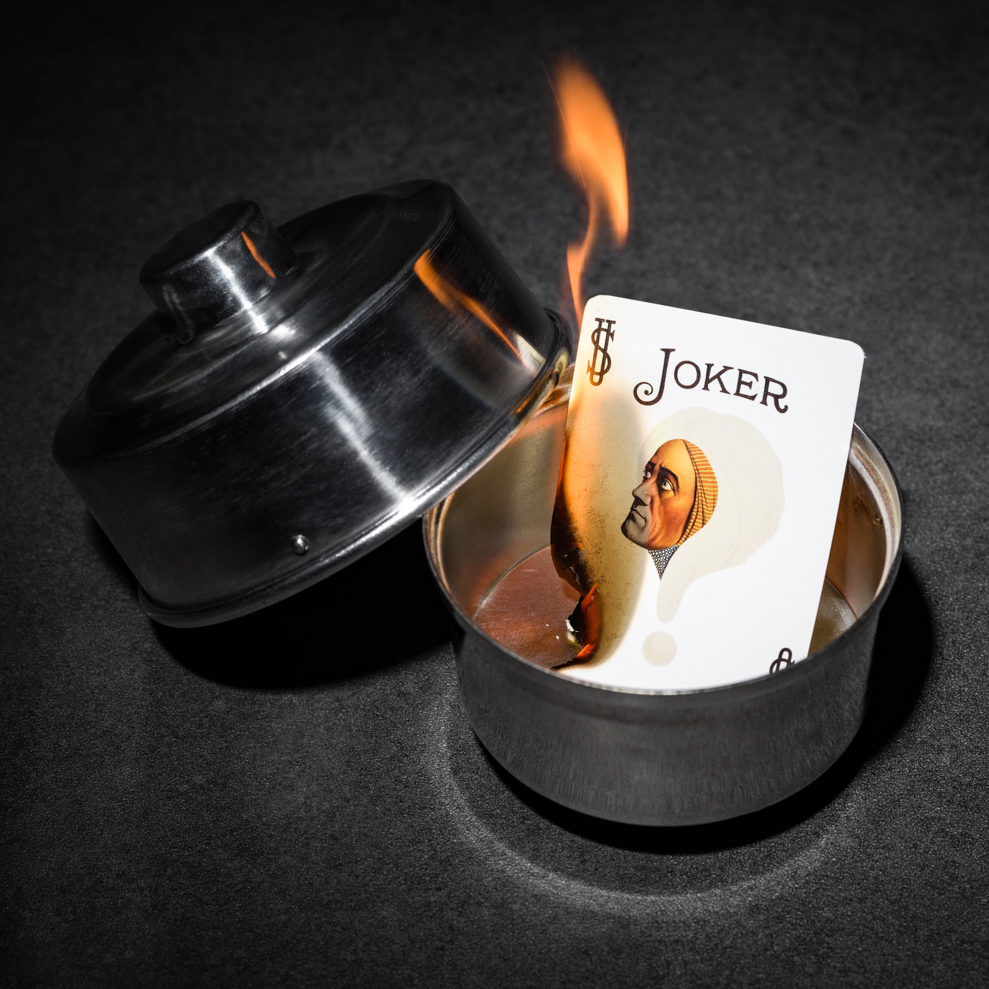 Photograph of a burning joker card in a silver dish. On the card is the face of the 1920s mind reader, Alexander.