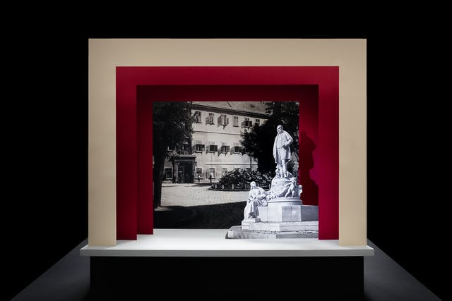 Photograph of a simple theatre stage set, made out of card. The background surrounding the stage is black. The stage floor is white and the framing of the stage is made out of 3 square edged arches, each one smaller than the other, receding backwards. The first arch is cream coloured and the other two are a red. On the stage is a small cut out photograph of a grand statue man with a beard from the early 20th century. Behind him forming the backdrop is a black and white archive photograph of a the outside of a hospital building.