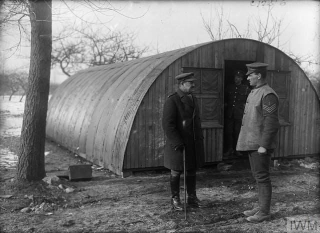 Photo of a curved metal hut with soldiers standing out the front.