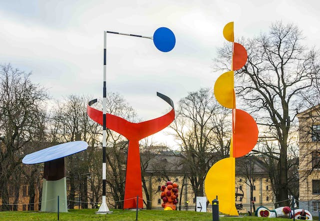 A large multipart open-air sculpture, featuring metal shapes includiding circles and semi-circles in orange, yellow, red and blue.