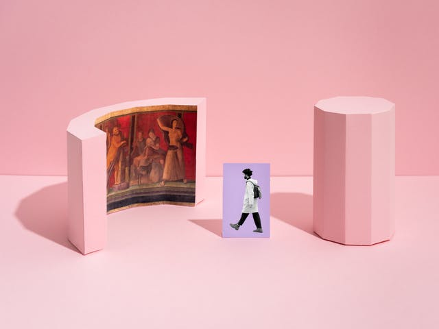 Photograph of a set built scene. The scene is made out of a light pink horizontal surface against a light pink vertical background with a thin horizon line. On the horizontal surface are two pink three dimensional shapes. The shape on the right is a tall thin shape with ten vertical sides. The shape on the left is semicircular with a Roman fresco visible on the inside curve. In the centre of the image is a rectangular flat purple card standing upright, on which is the black and white image of a man in full length wearing a backpack walking towards the fresco.
