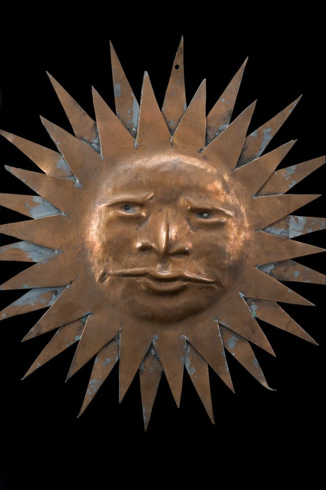 Image of copper Sun-shaped sign with a face
