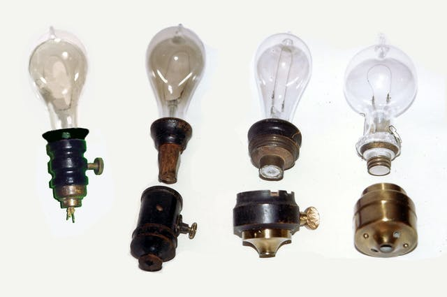 Colour photograph of four light bulbs with single curved wire filaments