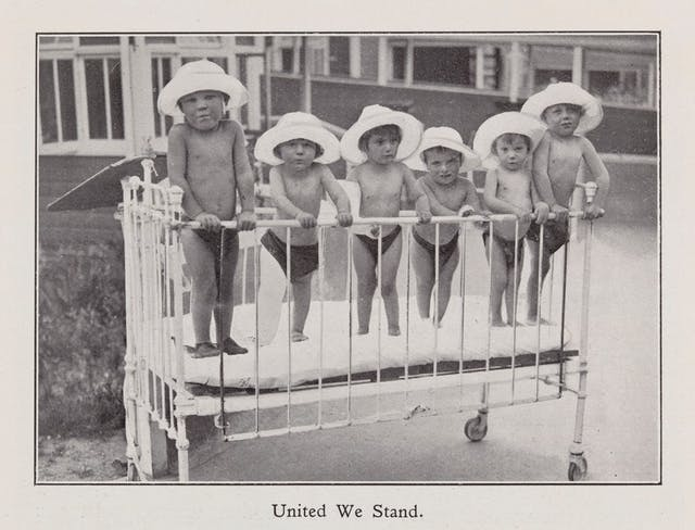 Black and white photo of six young children standing in a cot, wearing white sun hats.