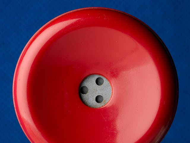 Photograph of a close up of an old red rotary telephone receiver
