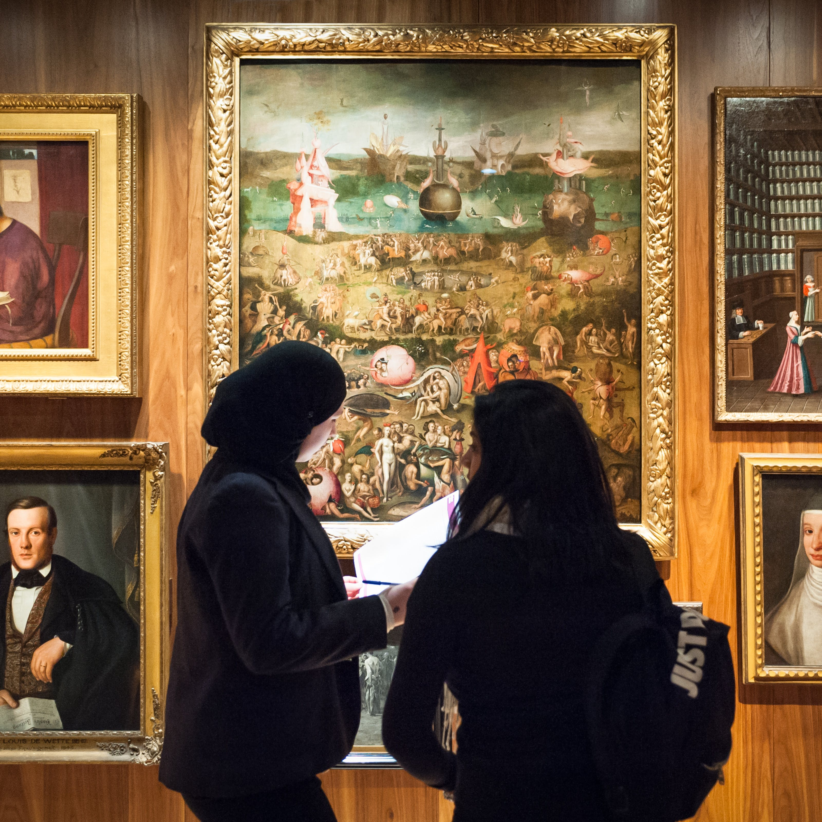 Photograph of the Medicine Man exhibition at Wellcome Collection showing a wall of oil paintings with two visitors standing in front.
