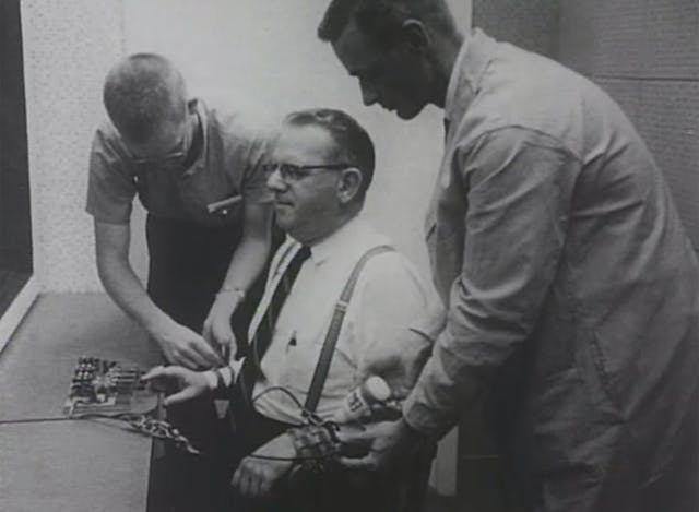 Two men attach wires to a subject in an experiment.