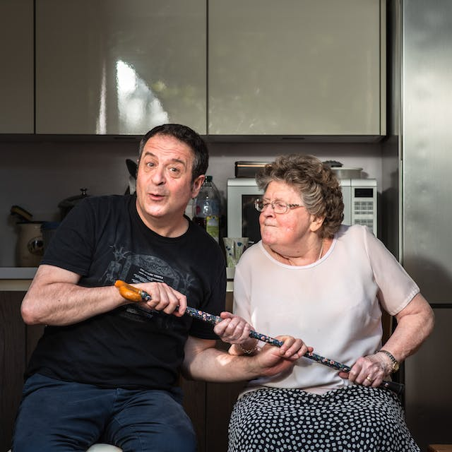 Photograph of a man and his mother sat side by side in a kitchen. The man wearing a black t-shirt and blue trousers is seated on the left has a cheeky look on his face, looking straight to camera. His mother on the right is wearing a pink blouse and blue patterned skirt and is looking towards him with pursed lips and a slightly annoyed and determined look on her face. She is thrusting her walking stick towards him with both hands, handle end first. Her son also has both his hands clasped to the stick. It looks as though they are both having a tussle over the stick. In the background are grey kitchen units, a microwave, the tap of the sink and a large silver fridge.