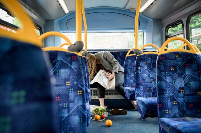 Photograph of a woman slumped on the back seat of the upper deck of a bus, a newspaper scrunched on her lap. On the floor in front of her, one of her shoes has come off and her bag of groceries has fallen over and a couple of oranges have escaped.