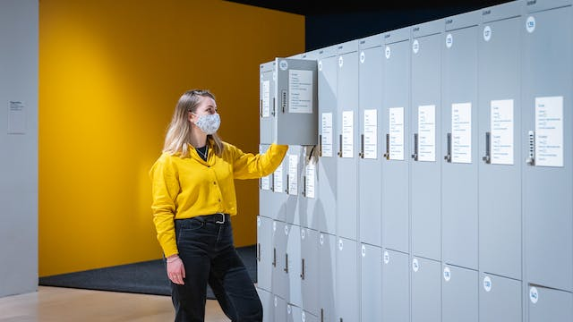 Photograph of a young woman wearing a face covering, a yellow shirt and black trousers, standing in front of a row of grey lockers. One of the locker doors is open and the woman is in the process of putting an item into the locker. Behind her is the yellow wall of the room.