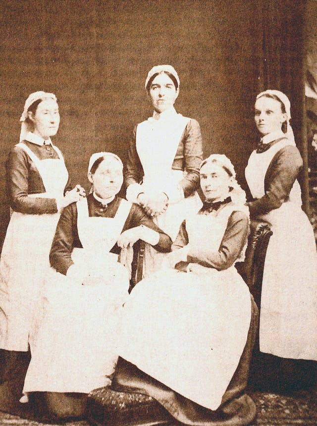 Photograph of five women, three standing and two seated in front of them. They wear Victorian clothing including caps, dark blouses, and white aprons.