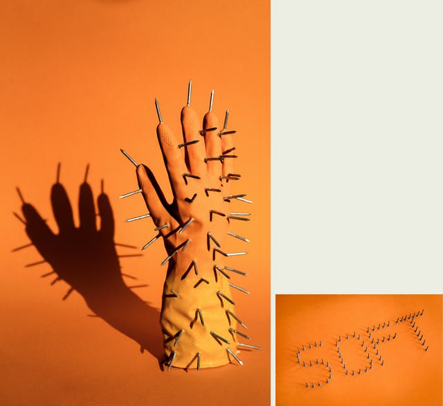 Photographic diptych, one large vertical image on the left and one smaller horizontal image on the right. The one on the left shows the right hand of a pair of rubber gloves. The orange and yellow glove is standing upright, fingers into the air, on an orange background. The glove is padded so it looks as if there is a hand inside it. Sticking out of the glove all over the surface are metal carpentry nails, points outwards. The scene is lit by a hard contrasty light which is casting a long dark shadow of the glove and nails onto the background. The image on the right shows the word