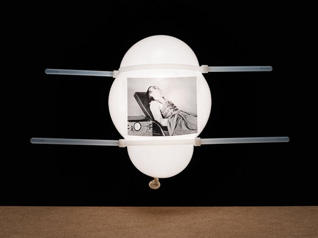 Photograph of a white inflated balloon against a black background, floating vertically above a wooden tabletop horizon line. The balloon looks like it is illuminated from within. On the side of the balloon is a rectangular, monochrome archive film still. The still shows a man lying propped upright on a bed with a contraption made of straps wrapped around his chest. To his right is a mechanical box which is connected to the chest contraption.  The two work together as an artificial ventilator. The balloon has 2 white cable ties around its surface which are deforming the balloon