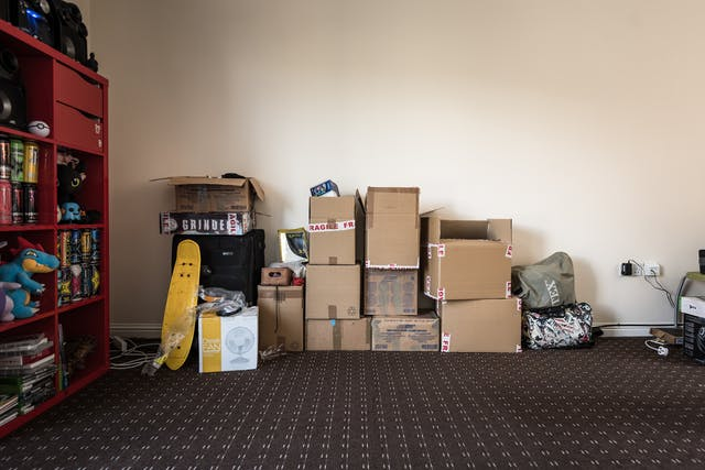 Photograph of unpacked boxes piled up against a wall inside a living room.