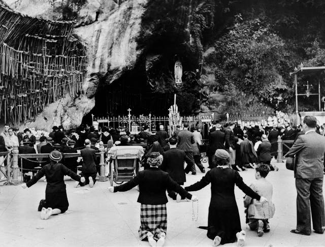 Black and white photograph of people kneeling at a shrine in Lourdes. Beside the worshippers, crutches can be seen hanging up.