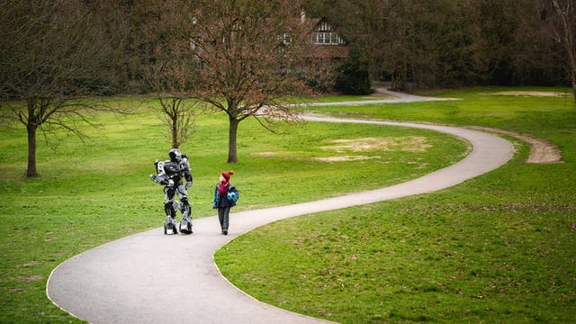 Photograph of a large robot walking and talking with a young boy in school uniform who