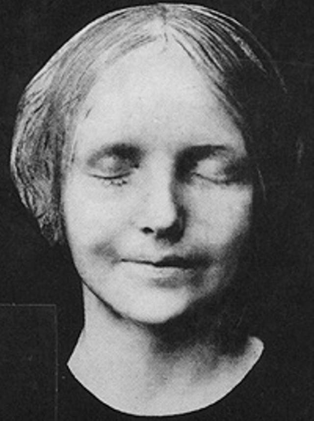 Black and white image of death mask of young woman. She has her eyes closed and has a faint smile.