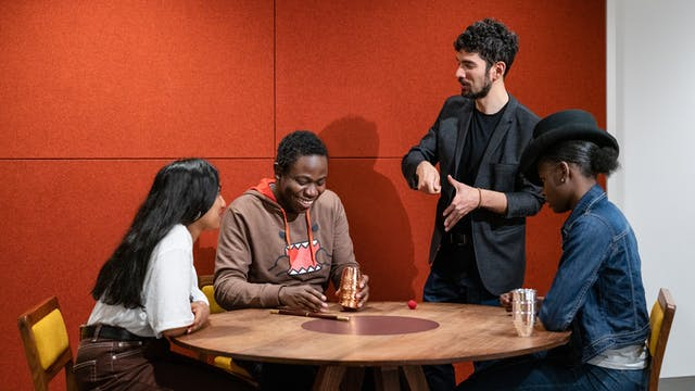 Photograph of 3 young participants sat around a table. One participant is being taught a magic trick by a magician standing next to them. On the table are magic tick cups and balls.