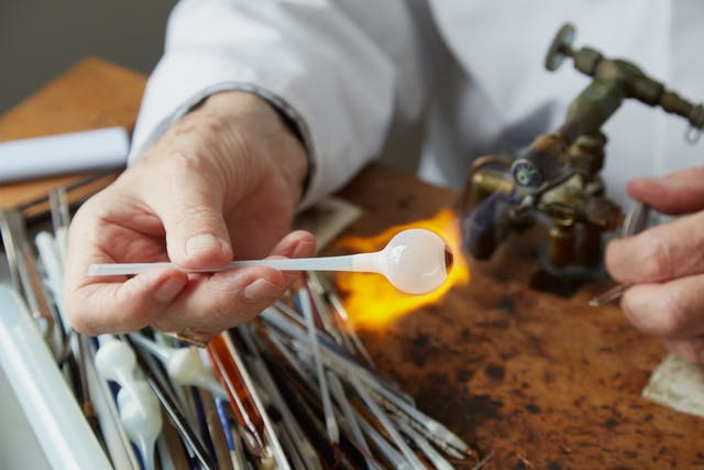 Photograph of the hands of a man in a white lab coat, holding a tube of white glass with a sphere resembling an eye ball at one end, to the flame of a gas torch. Next to him on the workbench are thin tools and more lengths of glass tubing.