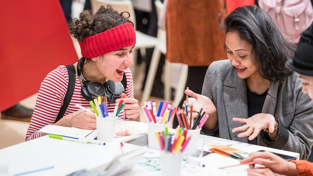 Photograph of two women sat at a table surrounded by coloured pens and pencils, undertaking a creative drawing workshop.