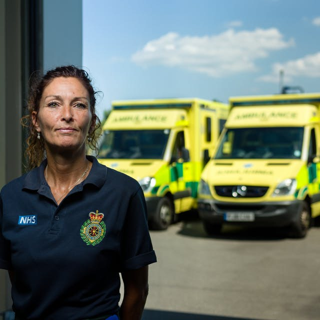Photographic portrait of Mandy English, paramedic, at Hull East Ambulance Station, with ambulances in the background.