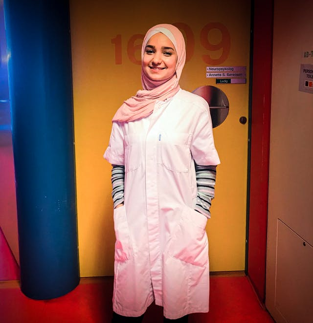 Photograph of a young woman wearing a head scarf and dressed in a medics coat. Behind her are the colourful doors and walls of a hospital.