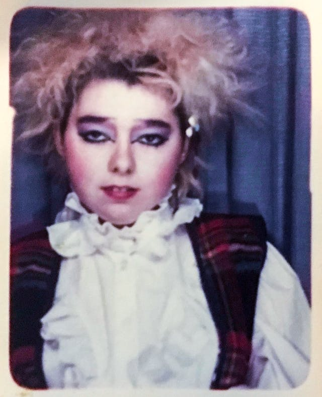 Photograph of a polaroid showing a young woman dressed in clothes from the punk era.