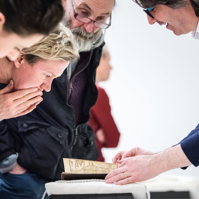 Photograph of a group of people examining library material on a table.