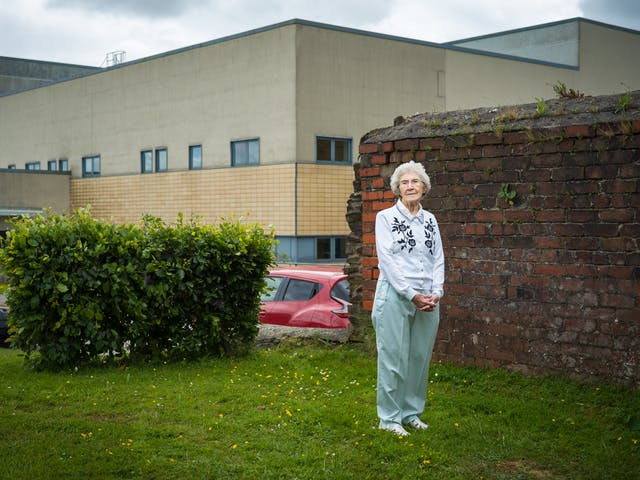 Photographic full length portrait of Joyce Thompson, retired nurse, outside the Royal Blackburn Hospital.