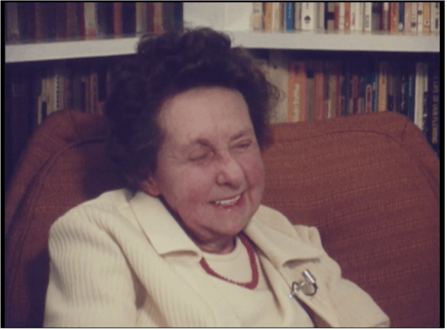 Film still of an older woman smiling. She