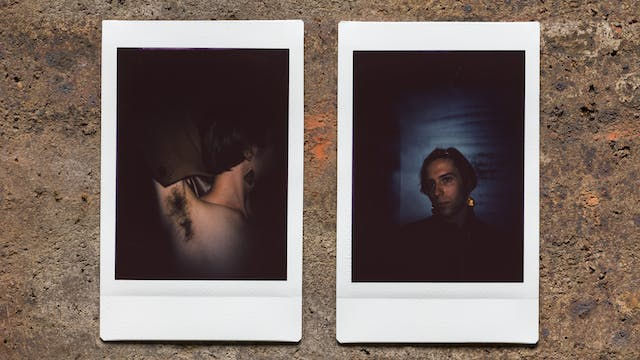 Photograph of two Instax Mini instant film prints in a line, resting on a textured brick surface. The two prints feature the same individual. The print on the left shows the individual emerging out of darkness with their left arm raised up up to show their armpit hair. The print on the right shows the individual