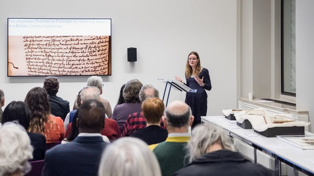 Photograph of a woman standing at a lecturn giving a talk to an audience. Beside her on the wall is a large screen showing her presentation slides.