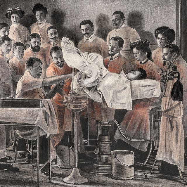 Pencil artwork drawn over an engraving of a photograph from the early 1900s which depicts a vaginal hysterectomy. The patient is lying on an operating table, her legs stirrups, covered in a white cloth. She is surrounded by 19 people who are either involved in the operation or just observing. The group is made up of mainly men. The whole scene is black and white apart from the gowns of the surgeons and observers which are tinted red.