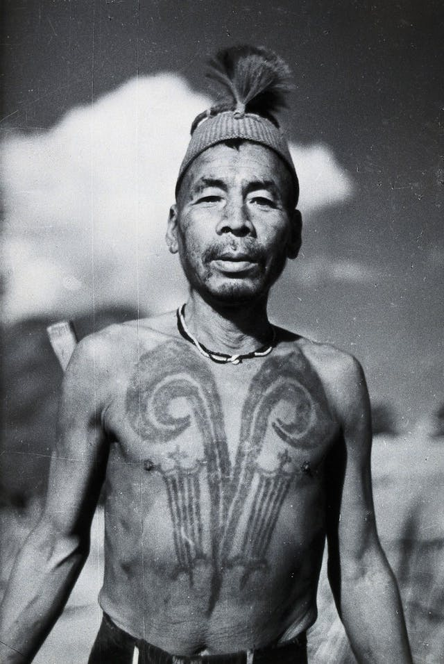 Black and white photo of a man with a chest tattoo