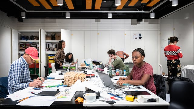 Photograph of the studio space at Wellcome Collection showing a group of young people working at a central table, which is covered in drawing and design material.