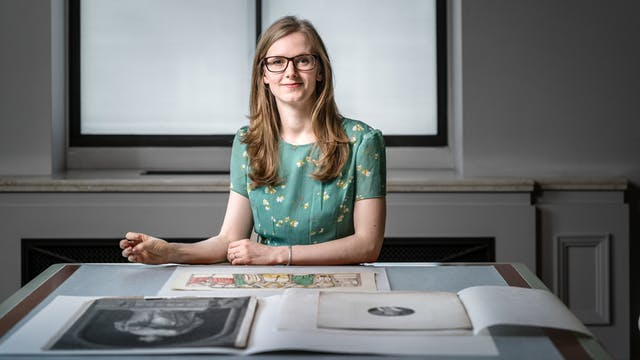 Photograph of Lauren Johnson sitting behind a desk in the Reading Room at Wellcome Collection, with a selection of collection items in front of her.
