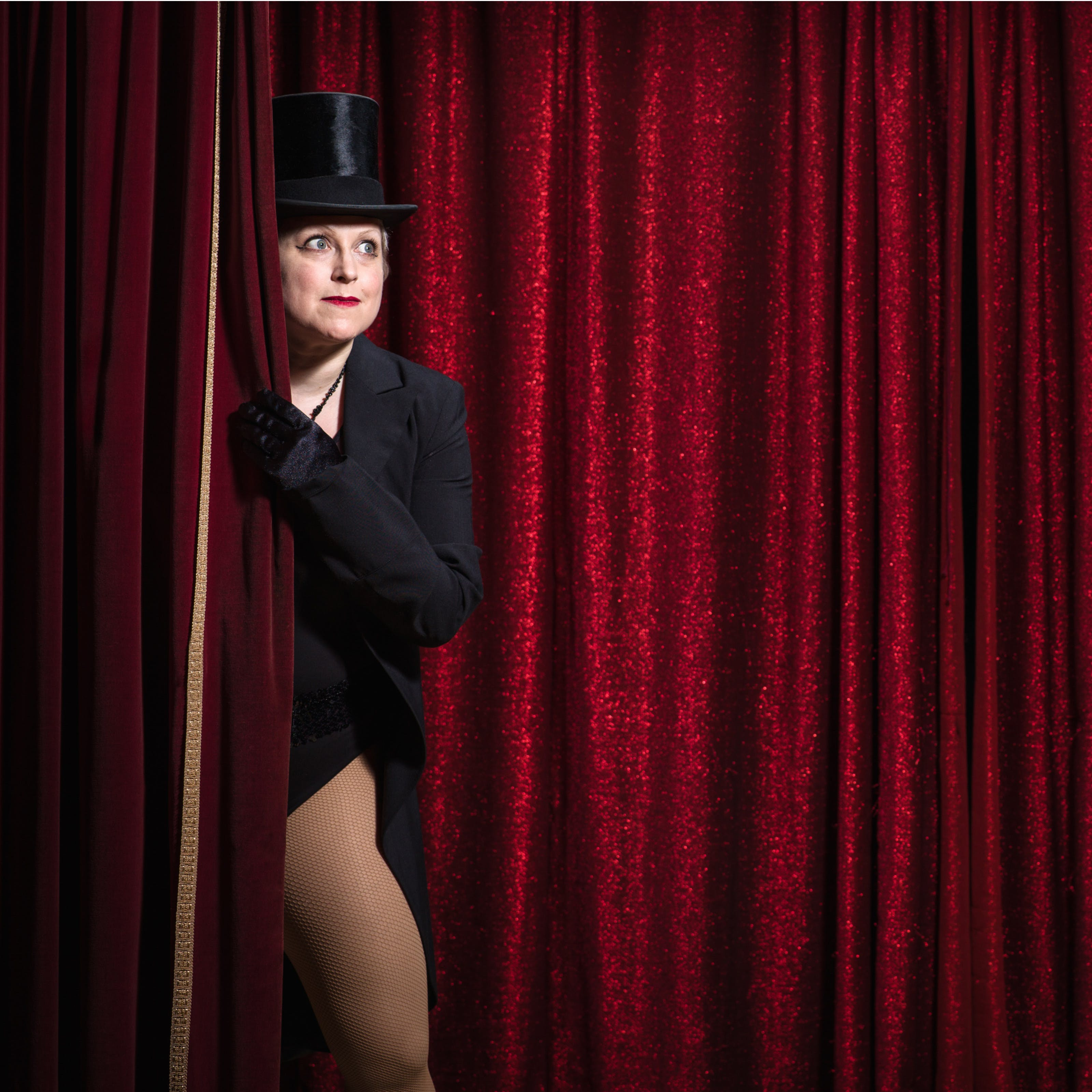 Photograph of a woman dressed in a top hat and tails peeping around the red curtain on a theatre stage. Behind her is another glittering red curtain.