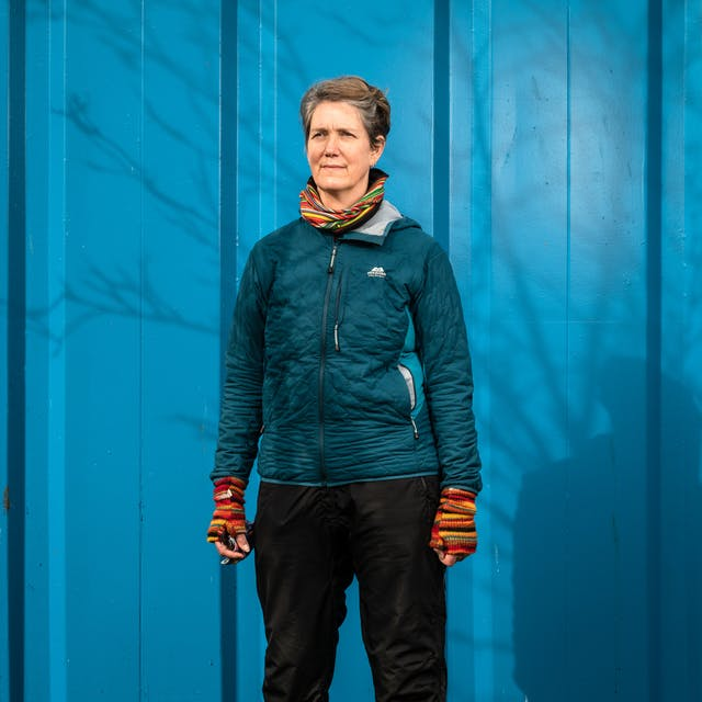 Photographic portrait of a woman from the knees up, wearing a blue insulated jacket, a colourful stripy scarf and colourful stripy fingerless gloves. She is stood against a blue shipping container and the shadow of a leafless tress is cast across her and the background, by the sun. She is looking off into the distance to the left of the camera.
