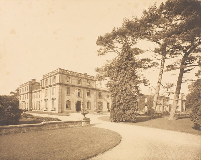 A page from a photo album showing Ticehurst Asylum, a grand building with a sweeping drive and mature trees in front of it.