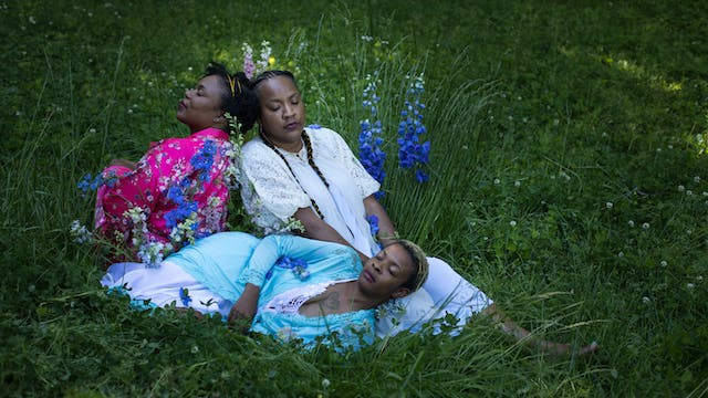 Portrait of Tricia Hersey in a field with her eyes closed leaning on two women. They are sleeping in nightwear among tall grass and flowers.